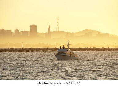 silhouettes of berkeley pier and the koit tower at sunset