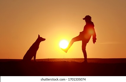 Silhouettes of a boy and a dog on a sunset background, a boy plays football with sun