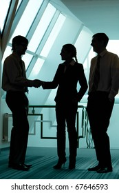 Silhouettes of business partners handshaking with man near by