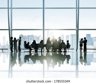 Silhouettes of Business People Around Conference Table with City Skyline