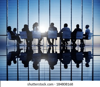 Silhouettes of business people in a conference room.