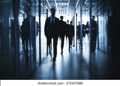 Silhouettes of business people going down office building corridor