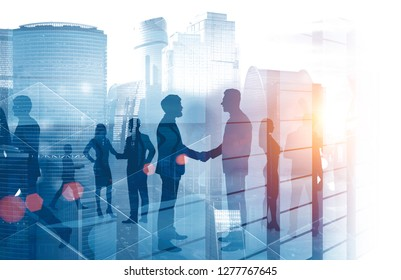 Silhouettes of business people shaking hands and discussing work over cityscape background with skyscraper. Toned image double exposure