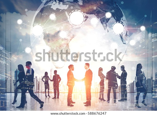 Silhouettes of business people shaking hands and walking against a morning cityscape. There is a world map and a network.  Elements of this image furnished by NASA. Toned image. Double exposure.