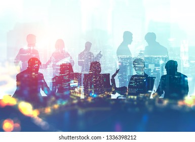 Silhouettes of business people sitting at meeting room table with their colleagues discussing work over night cityscape background. Double exposure toned image
