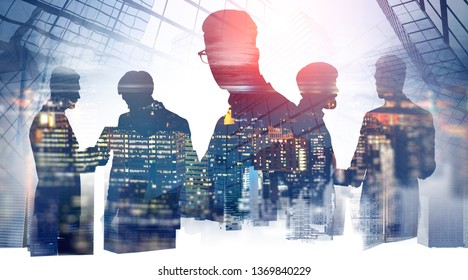Silhouettes of business people talking and shaking hands over skyscraper background with double exposure of night city panorama. Business lifestyle. Toned image