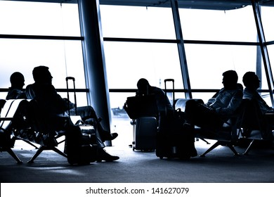 Silhouettes of business people traveling on airport; waiting at the plane boarding gates.