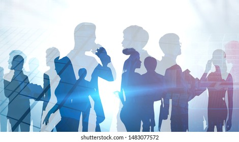 Silhouettes of business people working together over abstract city background. Concept of teamwork and communication. Toned image double exposure