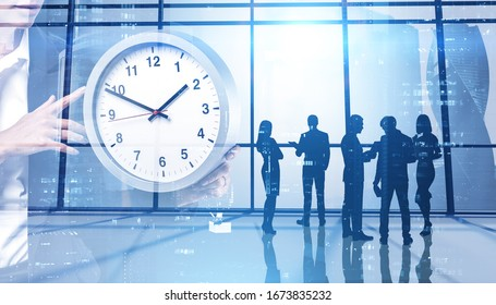 Silhouettes of business people working together in panoramic office with double exposure of woman holding big clock. Concept of time management and teamwork. Toned image