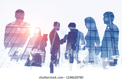 Silhouettes of business team members over white background with double exposure of skyscraper and upside down cityscape. Teamwork concept. Toned image