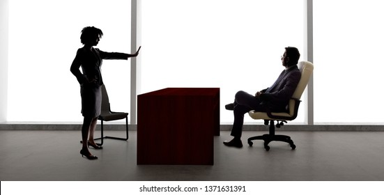 Silhouettes of a businessman and businesswoman fighting.  The business partners are having startup problems or a worker getting fired by a boss because of discrimination.
