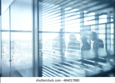 Silhouettes of businesspeople working in room with jalousie