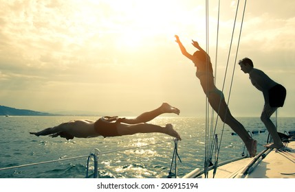 Silhouettes of children diving from the bow of a boat