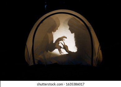 Silhouettes of children playing in camping tent at night making shadow puppets with flashlight enjoying summer holidays