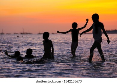 Silhouettes of children playing in the water at sunset