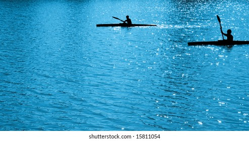 Silhouettes of children, rowing on blue water  on paddles