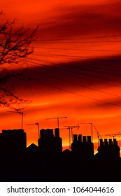 Silhouettes of chimneys and tv aerials with deep orange sunset