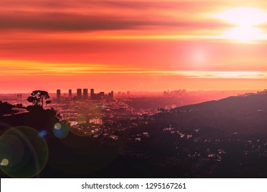 Silhouettes of city buildings, hills and trees in the distance and a hues of red and orange tones coloring the sky during sunset.