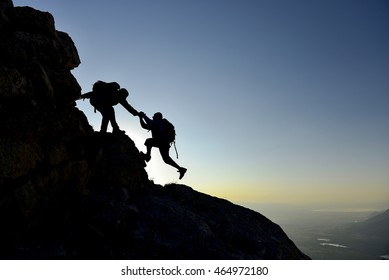 silhouettes of climbers who helped summit