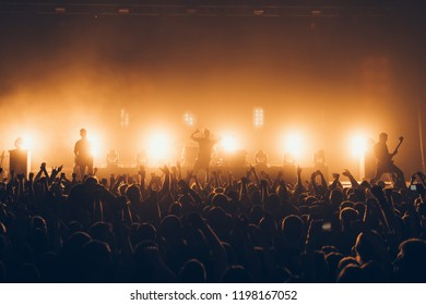 silhouettes of concert crowd in front of bright stage lights. A sold out crowd on rock concert. Crowd of fans at music festive. Party in nightclub.