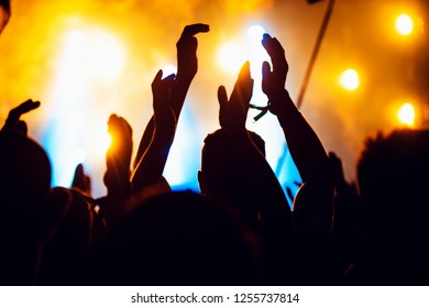 silhouettes of concert crowd in front of bright stage lights. cheering crowd of people with hands up on popular rock music concert. Dark background, smoke, concert spotlights.