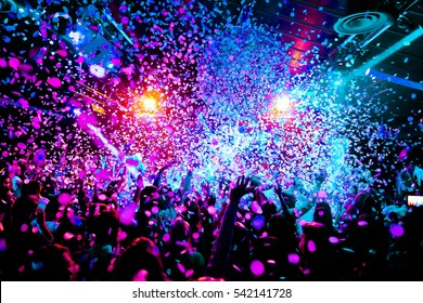 silhouettes of concert crowd in front of bright stage lights with confetti