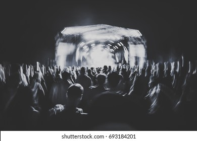 silhouettes of concert crowd in front of bright stage lights. Dark background, smoke, concert  spotlights. Group of people holding hands up at a concert