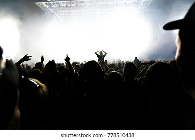 A silhouettes of concert crowd in front of bright stage lights. Dark background, smoke, concert spotlights