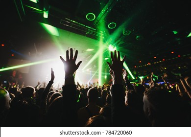 silhouettes of concert crowd in front of bright stage lights. Dark background, smoke, concert  spotlights