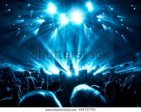 Silhouetten der Konzertbesucher vor hellem Lampenlicht