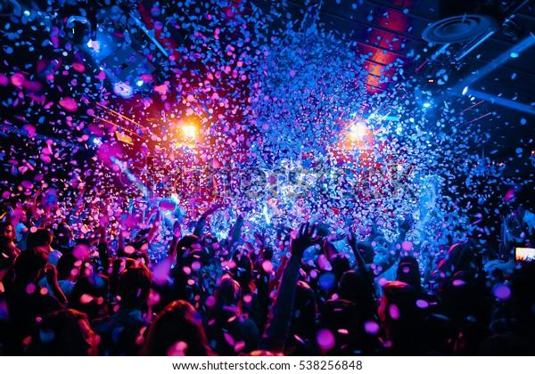 силуэты концертной толпы перед яркими сценических огней и конфети