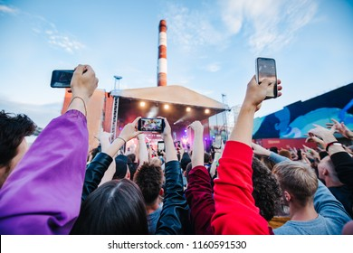 silhouettes of concert crowd holding smartphone, streaming in front of bright stage lights. background, concert  spotlights