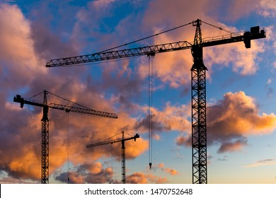 Silhouettes of construction cranes on the background of a beautiful sunset sky. Construction concept.