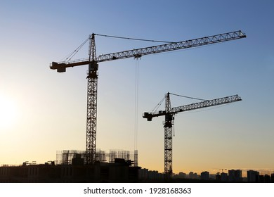 Silhouettes of construction cranes and unfinished residential buildings on sunrise background. Housing construction, apartment block in city