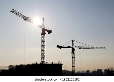 Silhouettes of construction cranes and workers on unfinished residential building against the sky and shining sun. Housing construction, apartment block in city