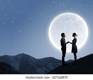 Silhouettes of couple against big moon at background