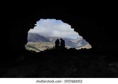 silhouettes of a couple backlit inside a cave in the Ansite Fortress in Gran Canaria, Spain