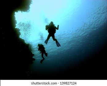 Silhouettes of couple of dvers swimming next to the wall