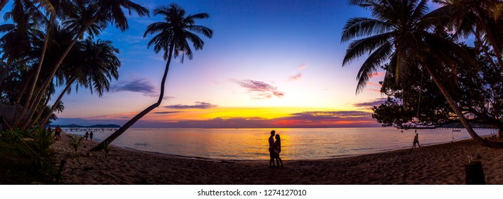 Silhouettes of a couple enjoying the sunset on the beach