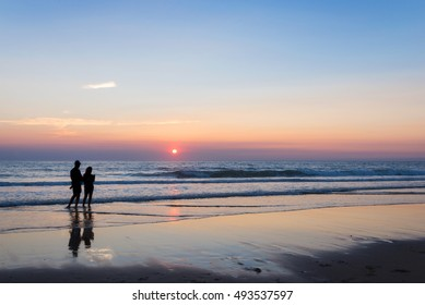 Silhouettes of a couple enjoying the sunset on the atlantic ocean, Lacanau France