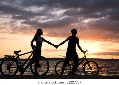 Silhouettes of couple holding each other by hands while walking down seashore with their bicycles at sunset