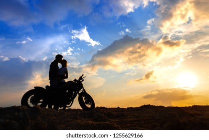 Silhouettes of a couple in love with a motorcycle on the background of the sunset sky