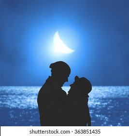 Silhouettes of a couple with lunar background. Moon, ocean and silhouettes of people are my work. No elements of third party.
