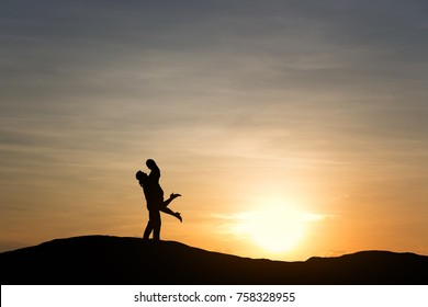 Silhouettes of couple man and woman in nature sunset background. Vintage filter. Love concept.