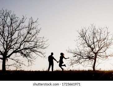 Silhouettes of a couple of man and woman outdoors, against sunset sky, walking between trees.