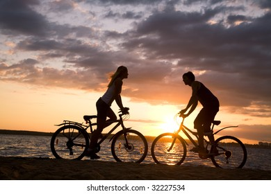 Silhouettes of couple opposite each other on their bicycles by the sea at sunset