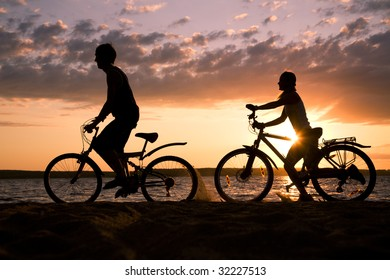 Silhouettes of couple riding their bicycles on seashore at sunset