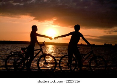 Silhouettes of couple stretching their arms to each other at sunset