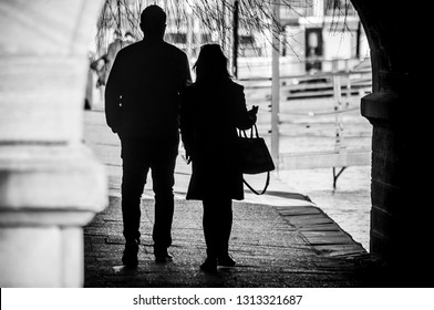 Silhouettes of couple walking under bridge in border river