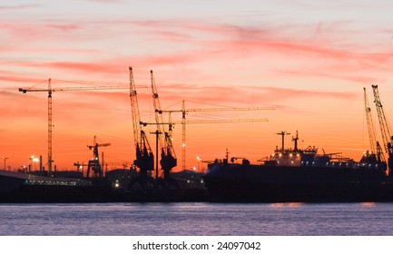 Silhouettes of cranes in the harbour by evening light